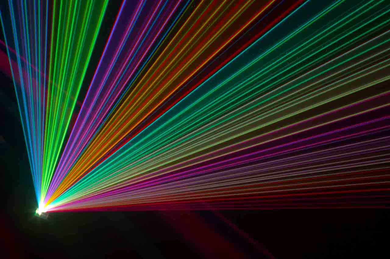 Ein farbstarker Laser wirft seine Lichtstrahlen eindrucksvoll im Takt der Musik durch den dunklen Raum. Foto: weagle95/Shutterstock.com