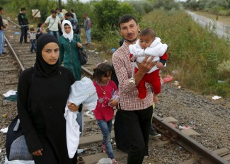 Syrian migrants walk along a railway track after crossing the Hungarian-Serbian border into Hungary, near Roszke