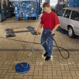 Using a rotary head pressure washer to remove weeds and moss from paving