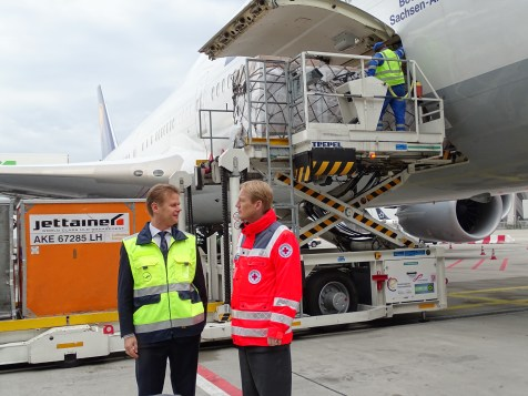 (l-r) Peter Gerber, Lufthansa Cargo CEO and chairman of the executive board speaking to German Red Cross general secretary Christian Reuter as the camp beds were being unloaded in Frankfurt.