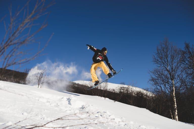 Uomo che salta con la tavola da snowboard