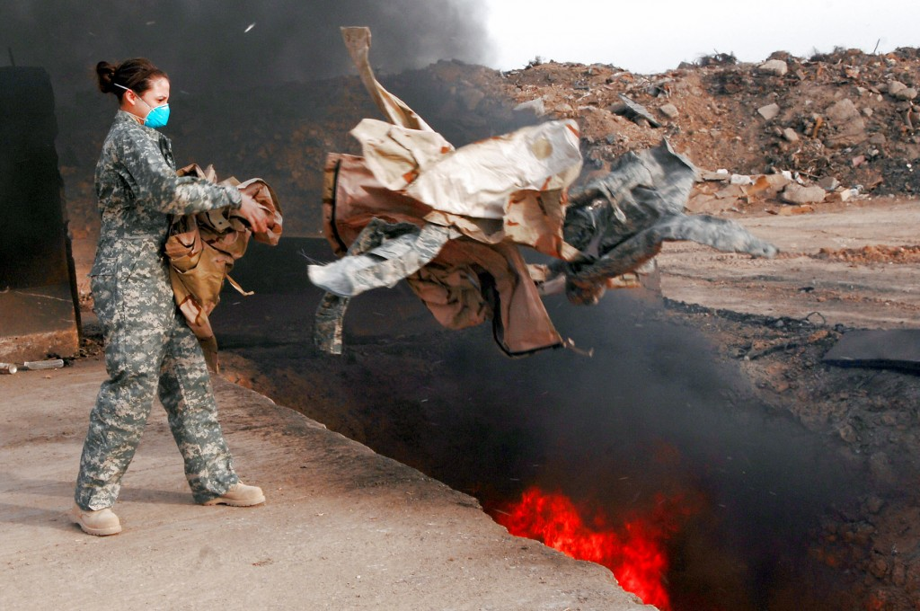 Senior Airman Frances Gavalis tosses unserviceable uniform items into a burn pit March 10 at Balad Air Base, Iraq. Military uniform items must be burned to ensure they cannot be used by opposing forces. Photo by (U.S. Air Force photo/Senior Airman Julianne Showalter
