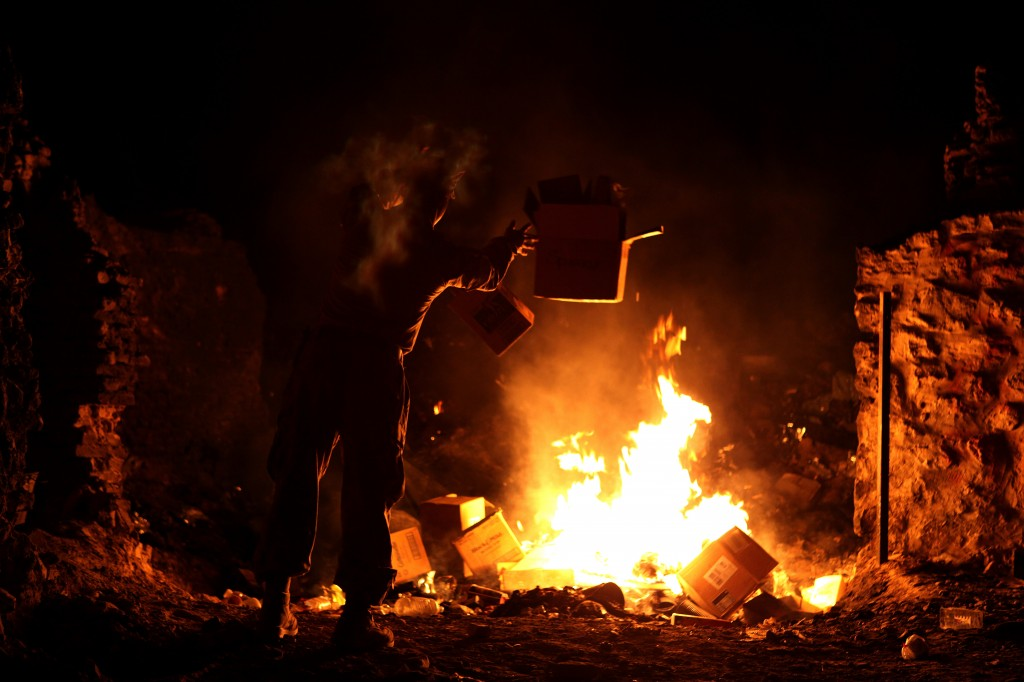A U.S. Marine at forward operating base Zeebrudge in Helmand province, Afghanistan, burns trash in March 2013. Photo by Sgt. Anthony L. Ortiz