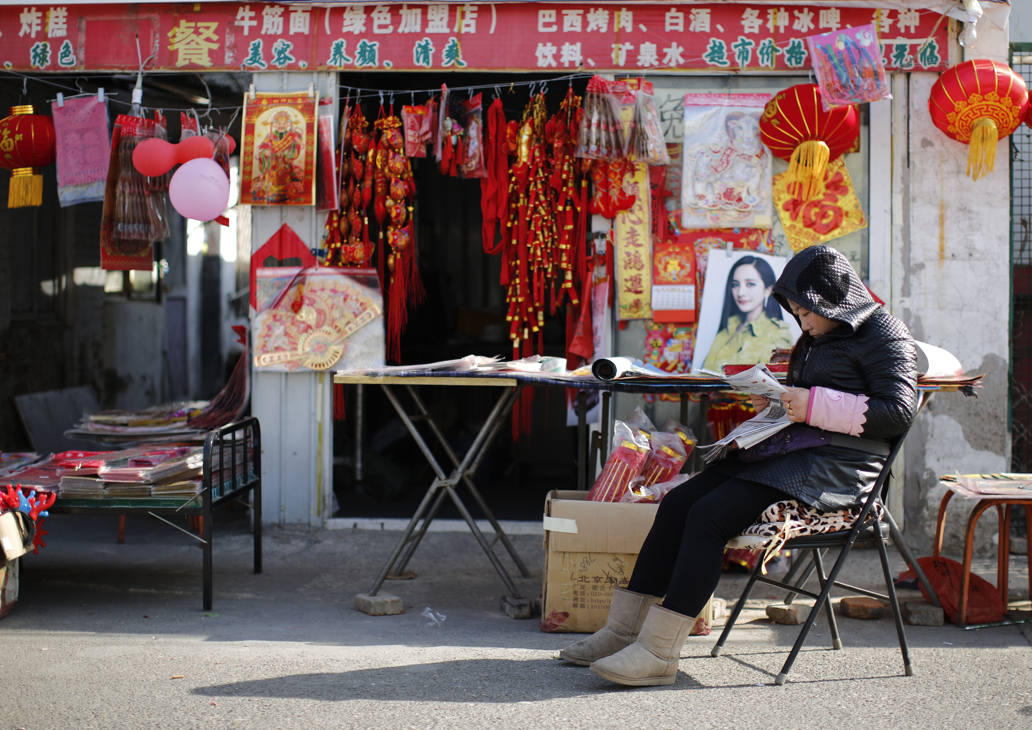 A vendor, selling traditional decorations for the upcoming Chinese Lunar New Year, reads a newspaper as she waits for customers at a migrant workers' village in Beijing February 12, 2015. Photo by Kim  Kyung-Hoon/REUTERS.