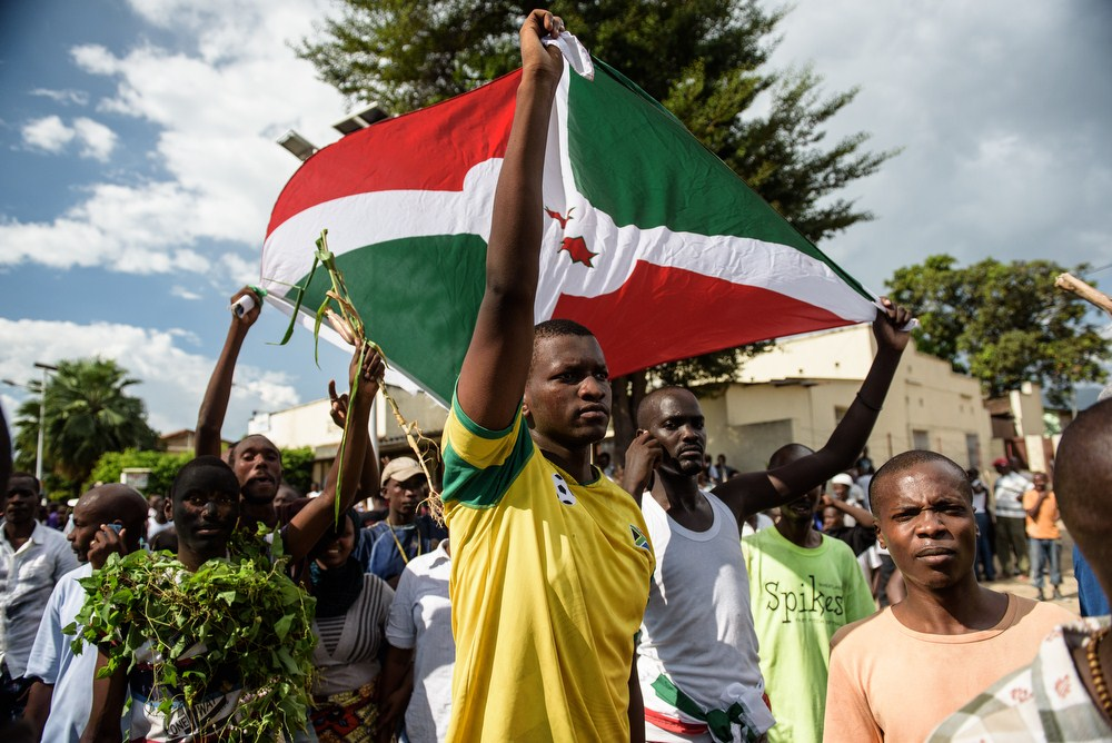Men hold Burundi's flag as people take to the streets to celebrate on Wednesday following the radio announcement by Major General Godefroid Niyombare that President Nkurunziza was overthrown. President Pierre Nkurunziza disputes the claim. Photo by Jennifer Huxta/AFP/Getty Images