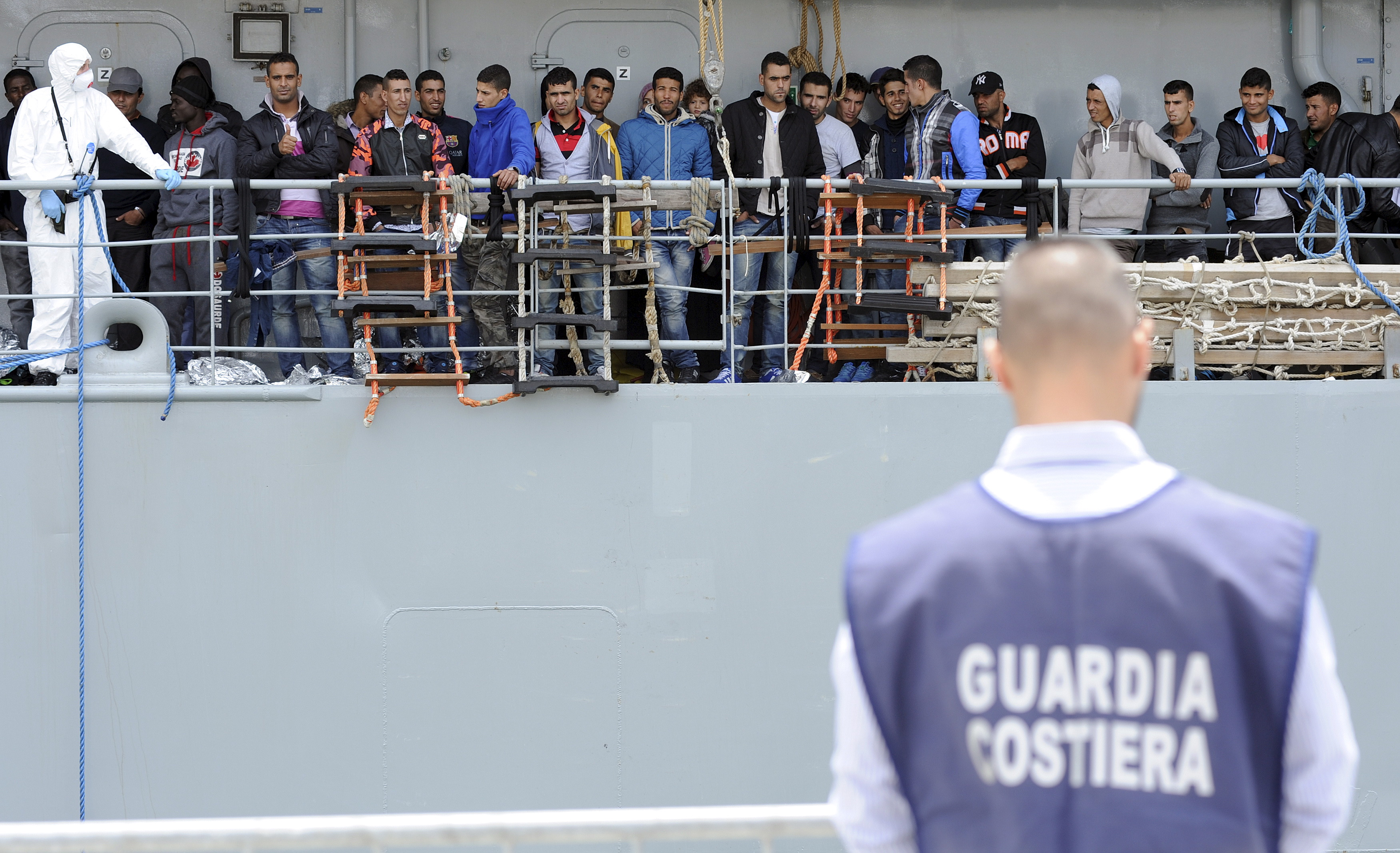 Migrants wait to disembark from the Irish navy ship LÉ Eithne as they arrives in the Sicilian harbour of Palermo, Italy, May 30, 2015. Photo by Guglielmo Mangiapane/Reuters