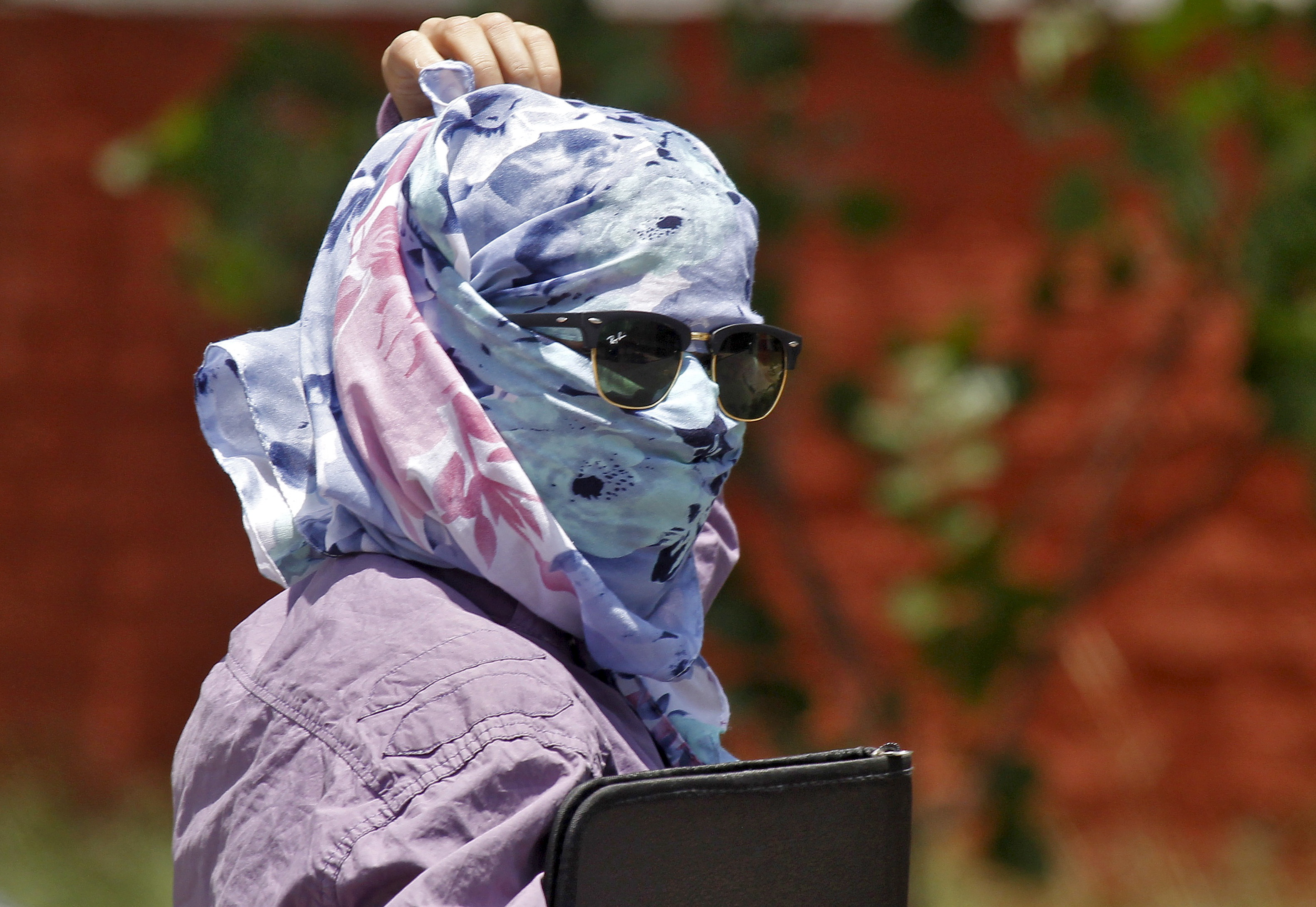 A woman walks along the road with her face covered to protect herself from sun stroke on a hot summer day in Chandigarh, India, May 28, 2015. Photo by Ajay Verma/Reuters