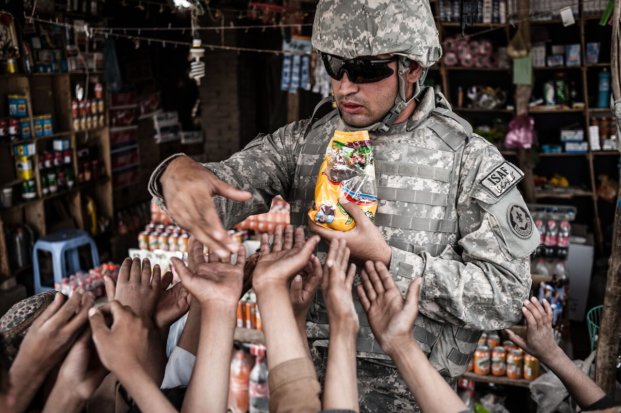 An interpreter for the U.S. Army hands out candy to local children at a rural gas station in Zabul Province in southern Afghanistan. Photo by Ben Brody/The GroundTruth Project