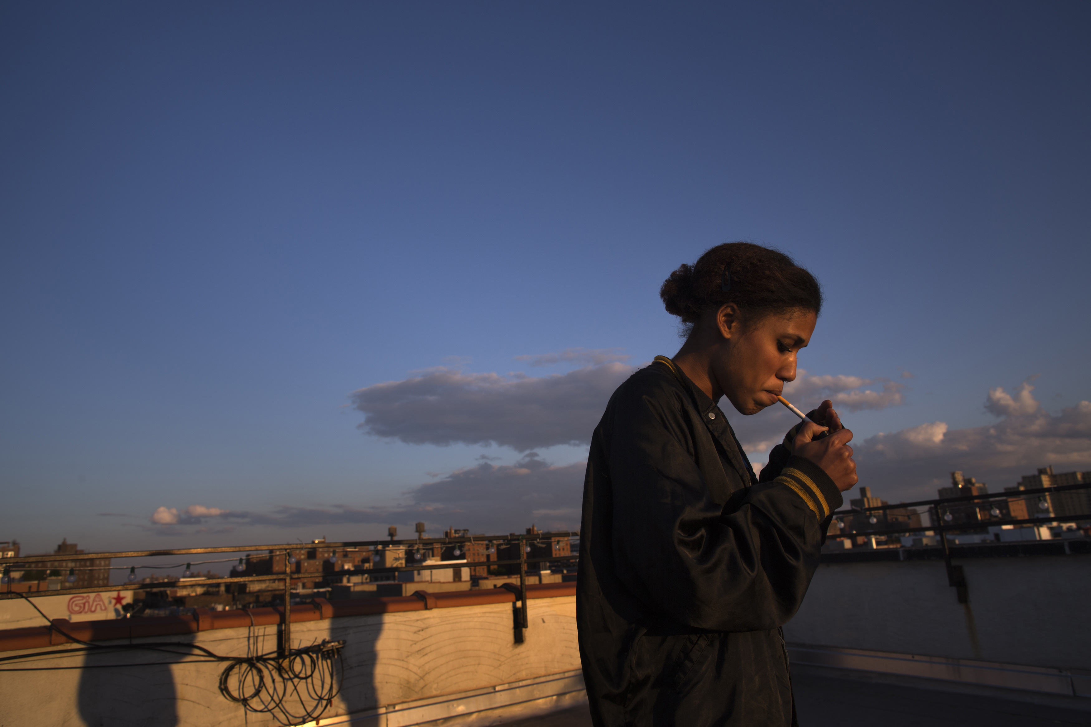 Ella Eliakim, 21, smokes on the roof of her apartment building in Lower Manhattan, New York May 18, 2014. The minimum age to buy cigarettes and tobacco was raised to 21 in New York City on May 18, 2014, six months after the law was signed by former Mayor Michael Bloomberg. Picture taken May 18, 2014. Photo by Eric Thayer/Reuters