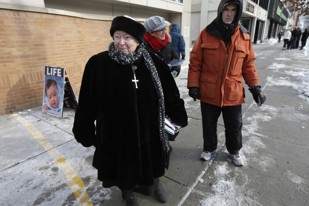 Anti-abortion protester Eleanor McCullen, of Boston, left, standing at the painted edge of a buffer zone outside a Planned Parenthood in Boston on Dec. 17, 2013. (AP Photo/Steven Senne)