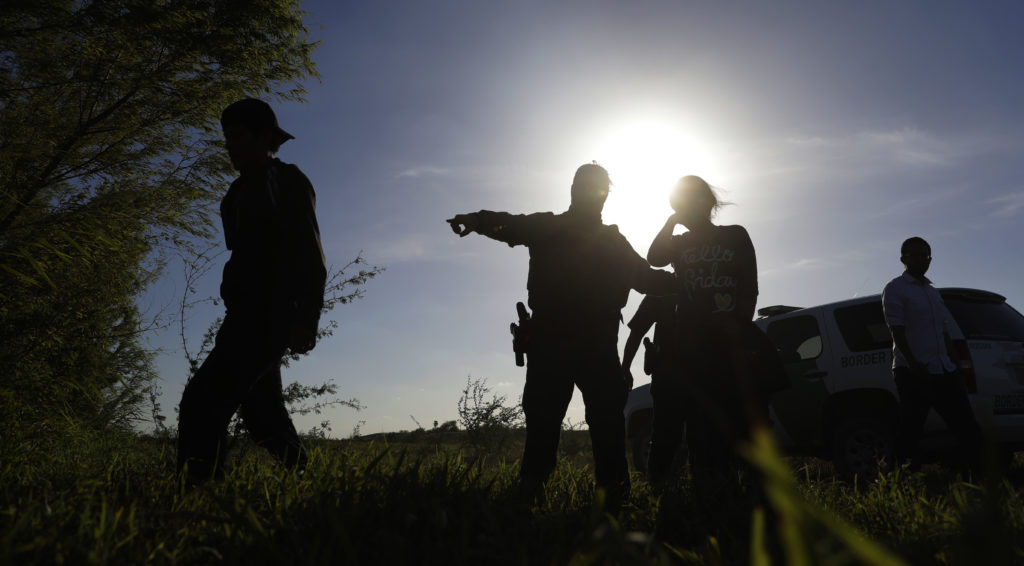 In this Aug. 11, 2017, photo U.S. Customs and Border Patrol agents pick up immigrants suspected of crossing into the United States illegally along the Rio Grande near Granjeno, Texas. (AP Photo/Eric Gay)