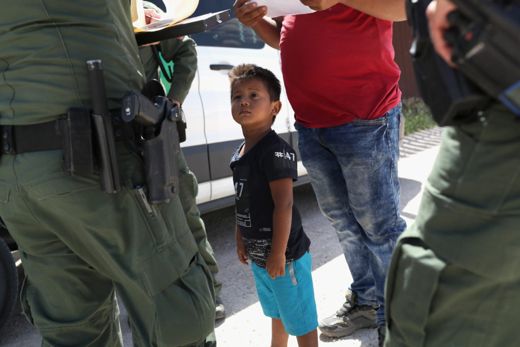 A boy and father from Honduras are taken into custody by U.S. Border Patrol agents near the U.S.-Mexico border on June 12, 2018.