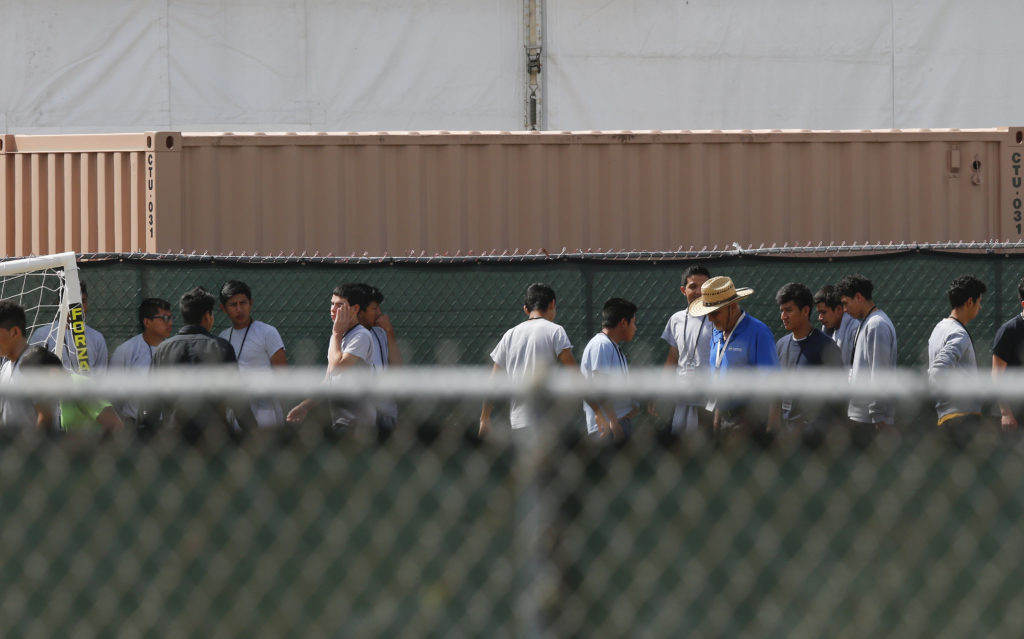 Migrant children walk outside a temporary shelter for unaccompanied children on June 22, 2018, in Homestead, Fla.