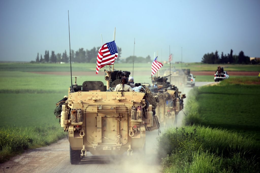 US forces, accompanied by Kurdish People's Protection Units fighters, drive their armored vehicles near the northern Syrian village of Darbasiyah, on the border with Turkey on April 28, 2017.