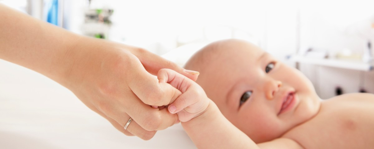 Mother holding her baby's hand in neonatal care office.