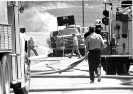 date unknown but possibly 1980s, firefighters hosing down trucks