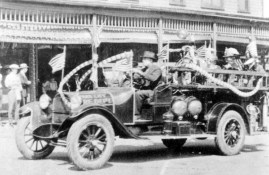 ca.1920s, William Berry driving Park City's first fire truck down Main Street during a parade (probably 4th of July or Labor Day)