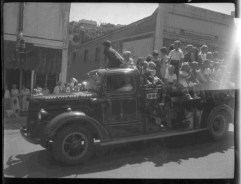 ca.1950s, kids riding fire truck in either 4th of July or Labor Day parade