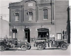 ca. 1930s, Two fire trucks and three men in front of Fire Department and City Hall building on Main Street. William Berry at left.