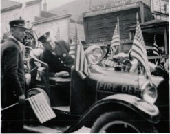 ca.1940s, Firemen get ready for parade (probably either 4th of July or Labor Day), with flags decorating their truck. On the 500-block of Main Street by Star Meat and Groceries. Man at left is Clarence Hays.