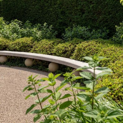 Bespoke oak bench surrounded by Rhododendron spheres, Centenary Garden, Exbury, Hampshire