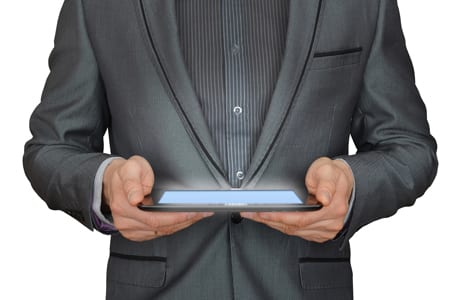 Cropped picture of a man's upper chest holding a glowing computer tablet with both hands