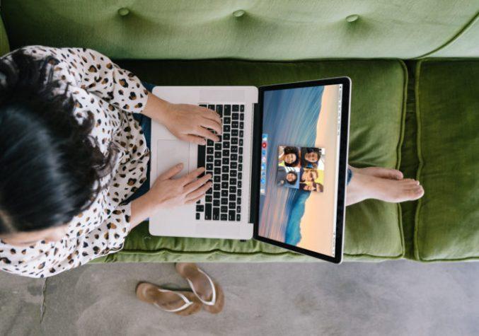 Zu sehen ist aus der Vogelperspektive eine Frau, die mit ausgestreckten Beinen auf dem Sofa sitzt und darauf ihren Laptop hat. Auf dem Bildschirm sieht man die Anwendung Houseparty. Bild: Unsplash/Allie Smith