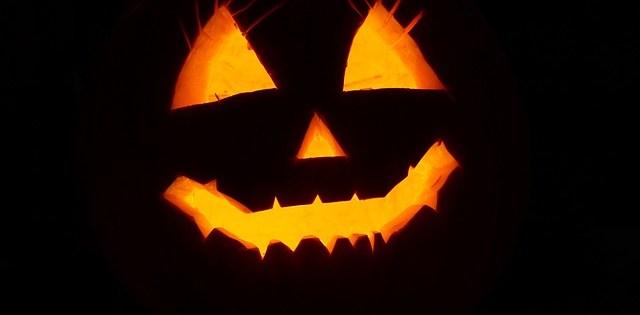 in questa foto si vede una zucca di halloween al buio illuminata da una candela riposta al suo interno
