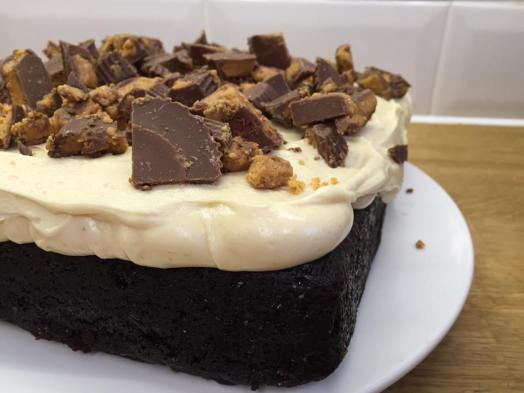 Chocolate Guinness cake with peanut butter frosting, topped with Reese's Cups!