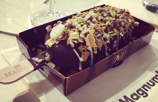 Jack's Magnum - peanut butter dipped, covered in gold flakes, pistachio, black lava salt, and drizzled in white chocolate.