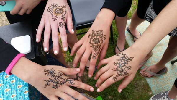 Four hands, each with a different smallish floral henna design