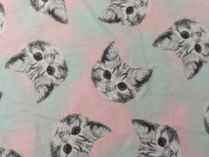 fabric with black and white kitten faces on pink and teal background