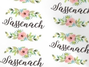 """pink and blue flower with green leaves borders """"Sassenach"""" in black cursive script on a white background"""