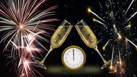 New year fireworks with midnight clock and champagne glasses