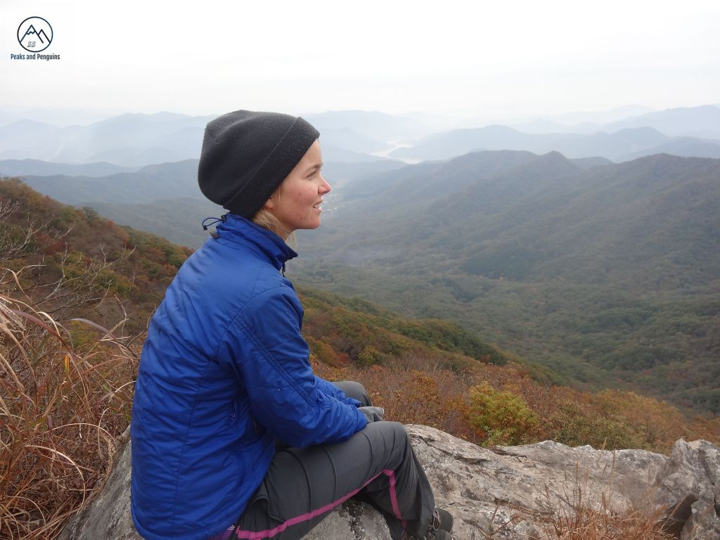 An image of the author sitting on a rock high above a valley carpeted in autumn colors. She is gazing ridges and valleys that are out of view.