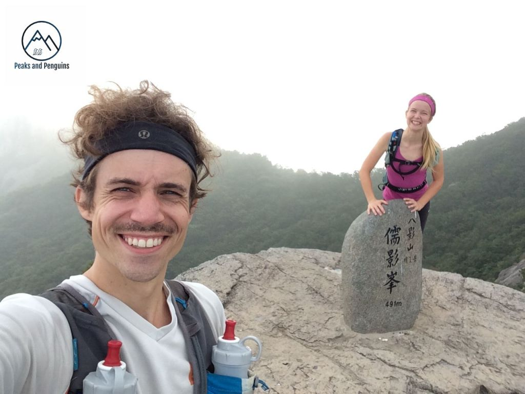 An image of the author and her husband on the first peak of Paryeongsan. The author's husband is in the front left side, smiling into the camera. The author stands behind and to the right, leaning over slightly with her hands on the summit stele. A forested ridge is visible through the mist behind them.