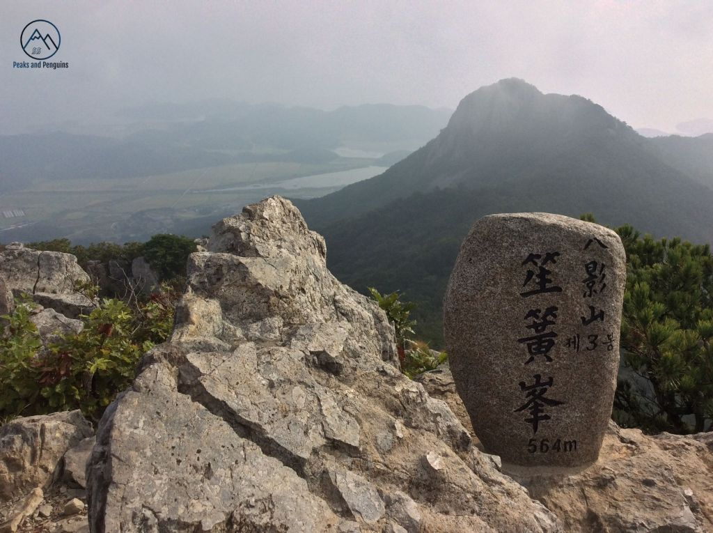 An image of the third summit along the Paryeongsan ridge. This image features the small summit stele on a sharp, rocky peak. A distant peak rises up from flat green rice farms,a dark hulking shape against the bright sunlit sky.