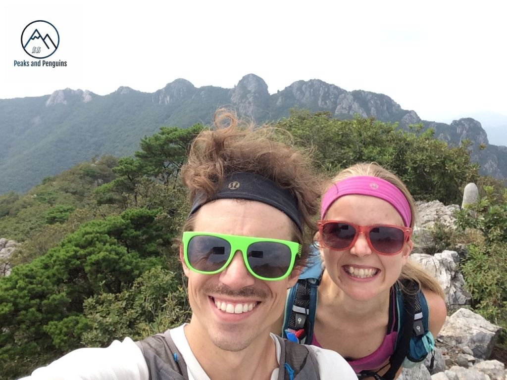 An image of the author and her husband on a rocky outcrop above a forest. Behind them, cutting across the image like a serrated knife are the eight jagged peaks of Paryeongsan. They are both grinning delightedly and the day is bright.