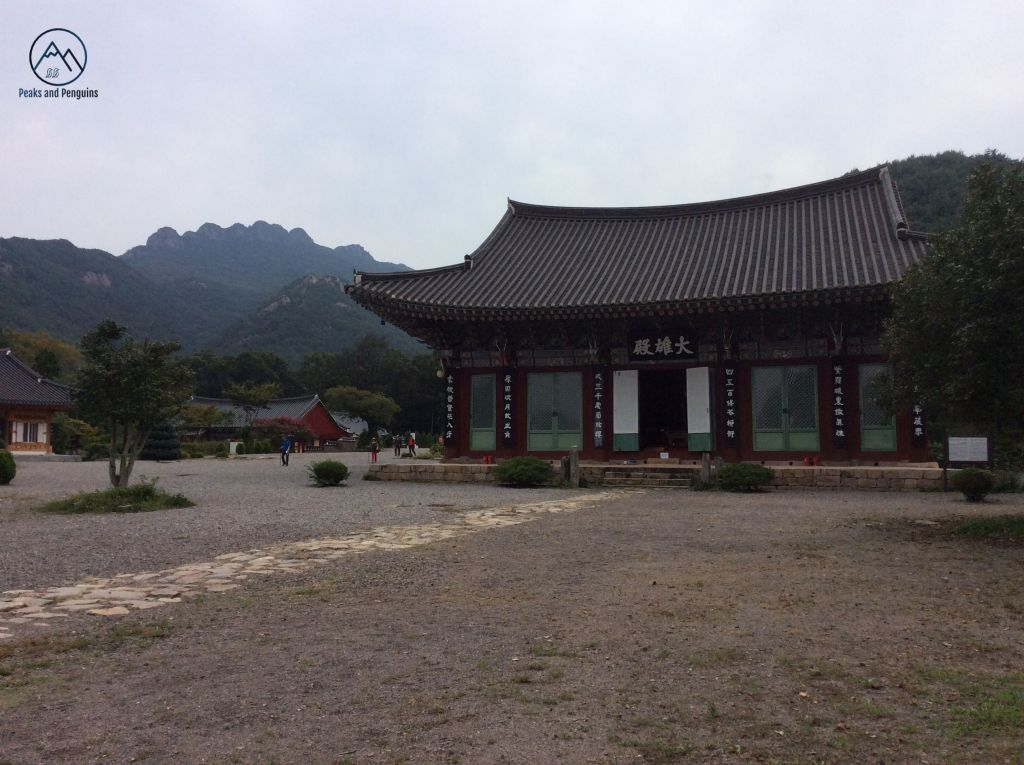 An image of the main hall at Neunggasa temple. It's colorfully painted walls and sloping black tiled roof are classical Korean architecture. The ground in front is mainly pebbles, with a trail of large slabs of rocks leading up to the open door of the temple building. To the left of the temple are the eight jagged peaks of Paryeongsan rising out of the forest.