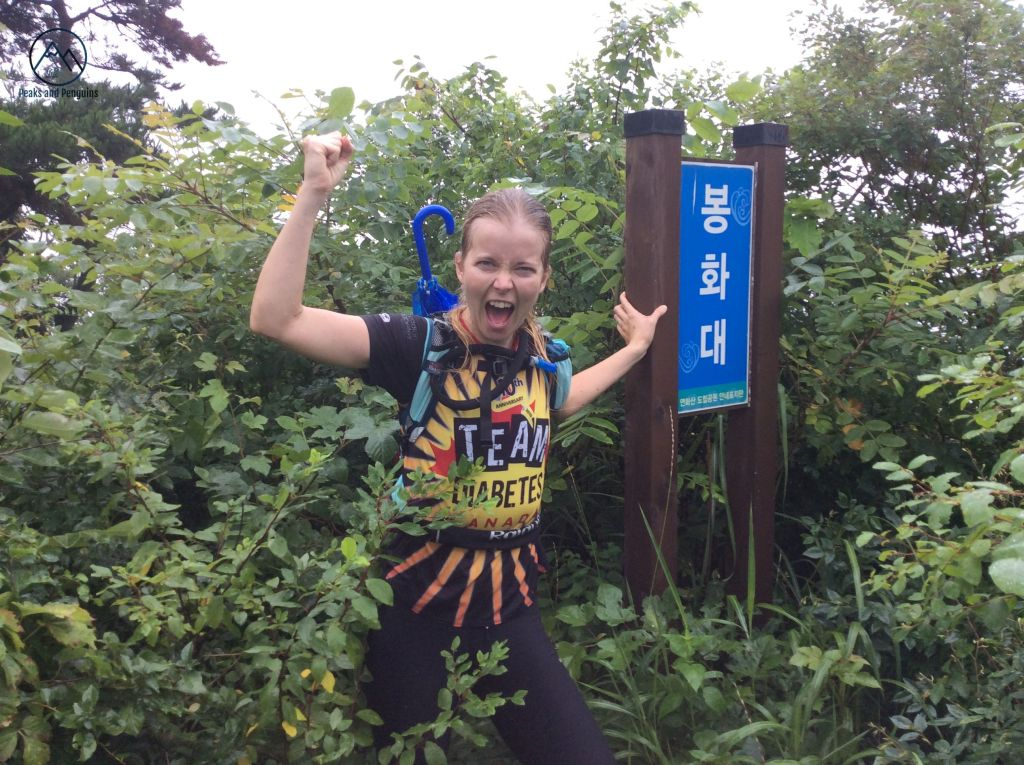 An image of the author, waist deep in the weeds. She's holding onto a large blue sign supported by two wooden posts with on hand. She has the other arm raised, her hand in a fist. She is wearing a running vest, with an umbrella tucked into it and popping up over her shoulder.