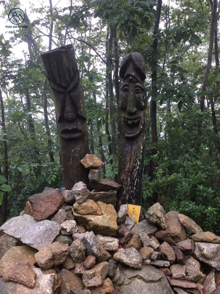 An image of two wood carvings rising out of a cairn of rocks. One of the carvings is all hard angles and sharp edges. It looks angry. The other one is carved with a smile, and has a head that could be either a mushroom or part of the male anatomy.