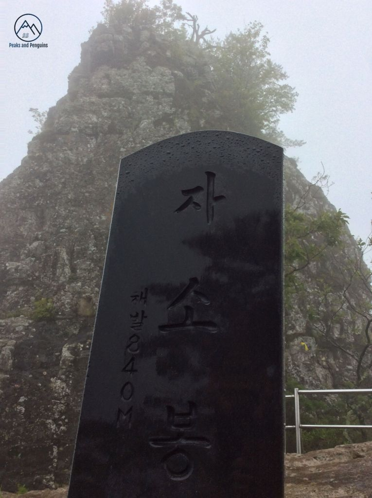 An image of the black summit stele on 840 meter Jasobong. The angle is low, so the stele rises upwards, framed by the jagged and inaccessible peak itself. The author's reflection is just visible on the shiny, damp black surface of the stele.