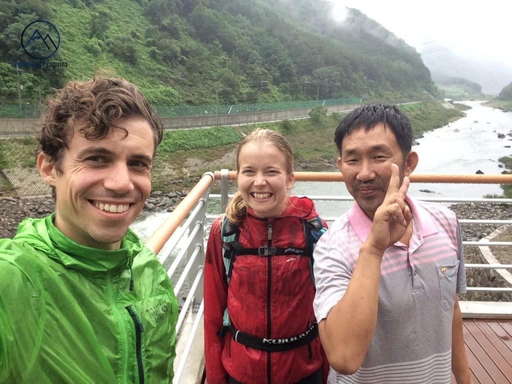 An image of the author, her husband and a local man they met at a restaurant in the tourist town. He offered to drive KnC to a bus stop. When they accepted, he took them on a bit of an area tour in his truck. One of the stops was at a brand-new pedestrian bridge over the river, where this selfie was taken.