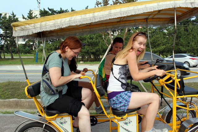 An image of the author and three others riding a bicycle built for four. The author is the only person looking at the camera. She's grinning delightedly and exaggerating the motions of riding a bike. The bike is yellow, with a yellow canopy above the peddlers.