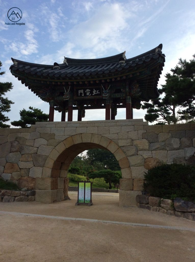 An image of the sight greeting visitors to Naksansa temple. A stone gate runs through the middle of the frame. A rounded opening for pedestrians and vehicles sits below an elaborate, gabled arch. The early morning sky above is bright and blue, peppered with feathery white clouds.
