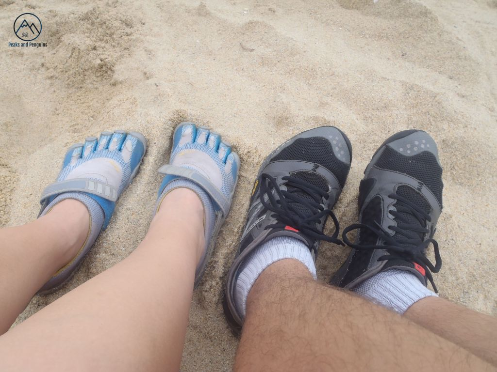 An image of four feet! The author and her husband's minimalist footwear is on display here: the author is wearing blue and white Vibram 5-fingers, and her husband sports black New Balance minimus. Both sets of feet are firmly planted in powdery sand.