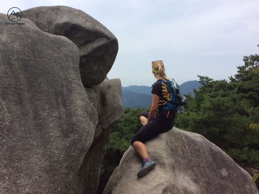 An image of the author seated on top of a large boulder. She is wearing a running backpack and has her back turned to the camera, looking out over the forested slopes of the mountain. A still larger boulder is to the left.
