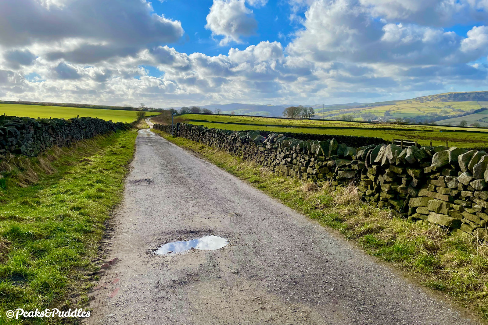 The surface of Over Hill Road begins to gently deteriorate as it leads you towards the peaks of the upper Goyt Valley in the distance, namely Shining Tor and Cats Tor.
