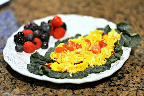 Whole30 compliant scrambled eggs and tomatoes in kale wraps.
