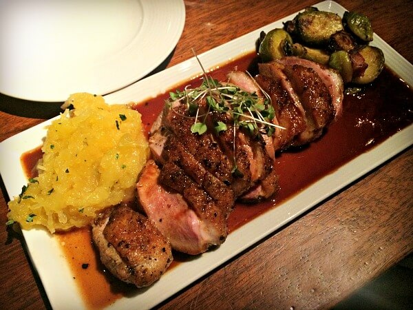 Duck breast with sides at Rooster's Wood Fired Grill in Charlotte